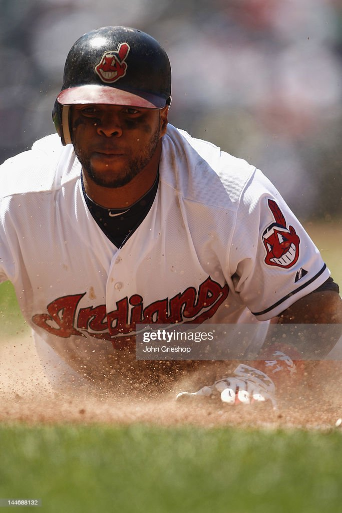 Carlos Santana #41 of the Cleveland Indians dives head first back into first base avoiding the double play during the game against the Seattle Mariners at Progressive Field on May 17, 2012 in Cleveland, Ohio. The Indians defeated the Mariners 6-5.