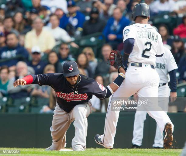 Carlos Santana of the Cleveland Indians has his arm bent backwards as it catches on the hip of Jean Segura of the Seattle Mariners who was safe at...