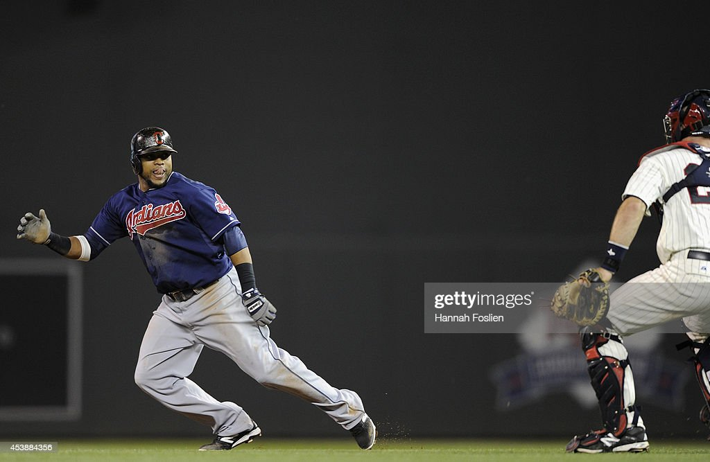 Carlos Santana #41 of the Cleveland Indians is caught in a rundown between first and second bases by Eric Fryer #26 of the Minnesota Twins during the sixth inning of the game on August 20, 2014 at Target Field in Minneapolis, Minnesota. The Indians defeated the Twins 5-0.