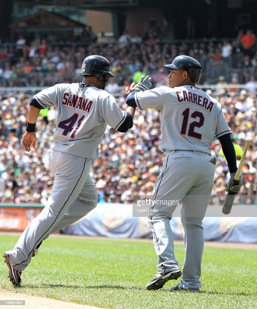 Carlos Santana #41 of the Cleveland Indians scores on Travis Haffner #48 single and is congratulated by teammate Ezequiel Carrera #12 during the first inning of the game against the Detroit Tigers at Comerica Park on August 5, 2012 in Detroit, Michigan.
