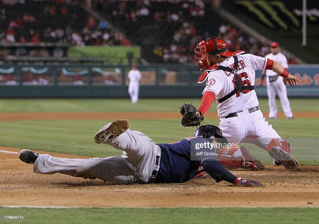 Carlos Santana #41 of the Cleveland Indians slides safely past catcher <a gi-track='captionPersonalityLinkClicked' href=/galleries/search?phrase=Hank+Conger&family=editorial&specificpeople=713039 ng-click='$event.stopPropagation()'>Hank Conger</a> #16 of the Los Angeles Angels of Anaheim and scores a run in the fourth inning at Angel Stadium of Anaheim on August 19, 2013 in Anaheim, California.