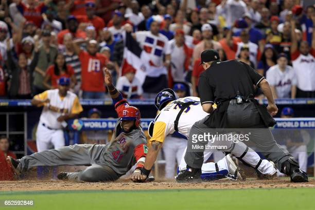 Carlos Santana of the Dominican Republic slides past the tag of Jorge Alfaro of Colombia in the 11th inning during a Pool C game of the 2017 World...
