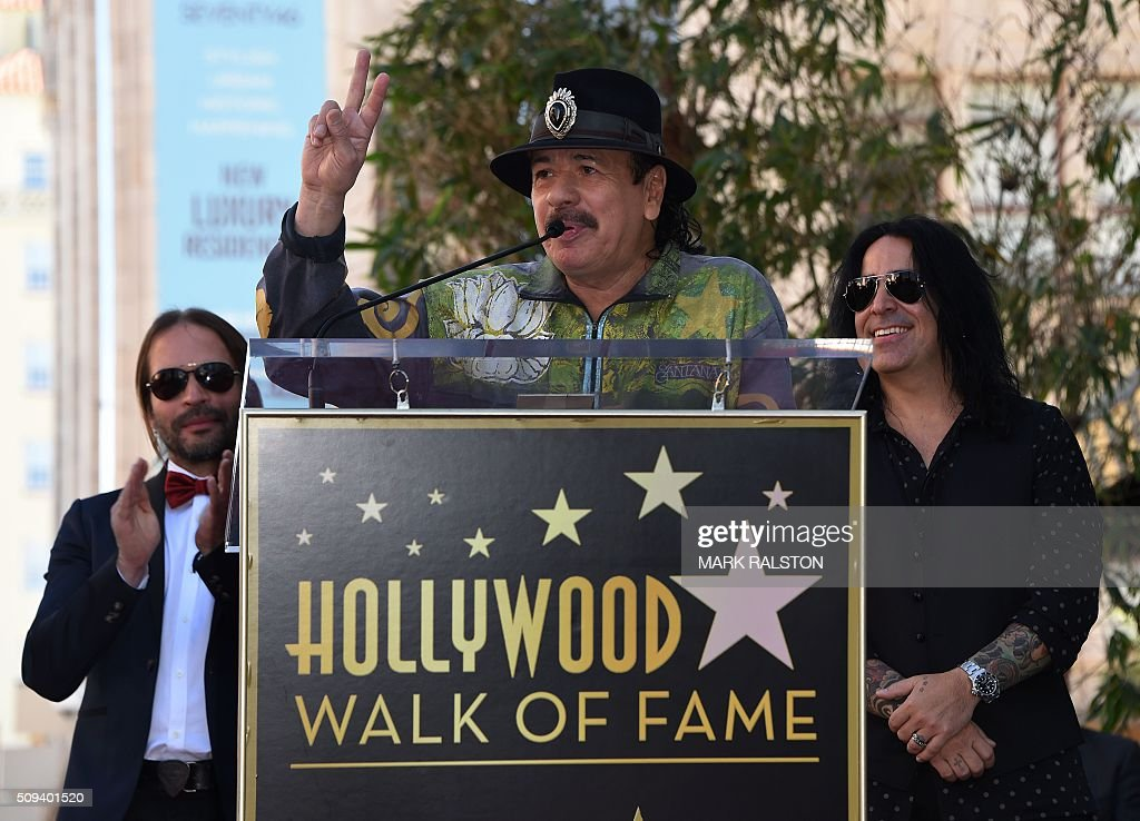 Carlos Santana speaks about the rock band 'Mana' at the ceremony honoring them with the 2,573rd star on the Hollywood Walk of Fame in Hollywood, California on February 10, 2016. / AFP / Mark Ralston