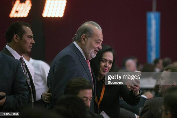 Carlos Slim Helu chairman emeritus of America Movil SAB and Carso Global Telecom SAB center smiles for a photograph with an attendee during the...