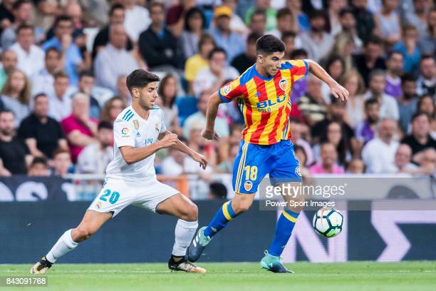 Carlos Soler Barragan of Valencia CF competes for the ball with Marco Asensio Willemsen of Real Madrid during their La Liga 201718 match between Real...
