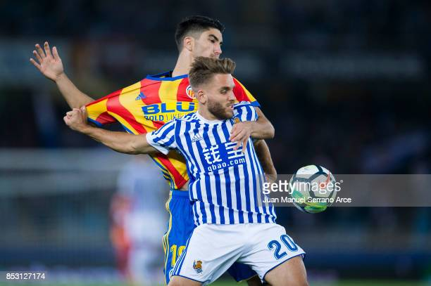 SAN Carlos Soler of Valencia CF duels for the ball with Kevin Rodrigues of Real Sociedad during the La Liga match between Real Sociedad de Futbol and...