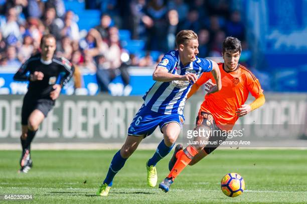Carlos Soler of Valencia CF duels for the ball with Marcos Llorente of Deportivo Alaves during the La Liga match between Deportivo Alaves and...