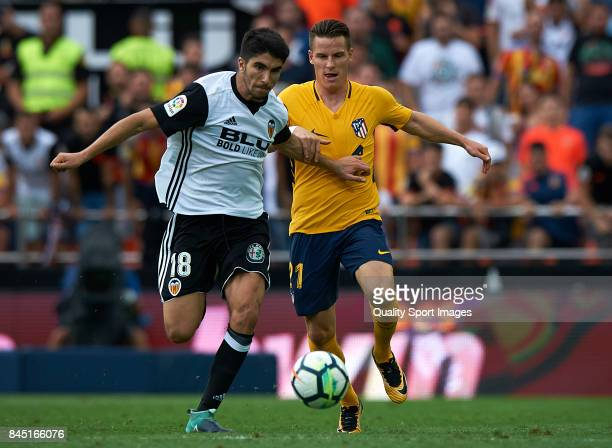 Carlos Soler of Valencia competes for the ball with Kevin Gameiro of Atletico Madrid during the La Liga match between Valencia CF and Atletico Madrid...