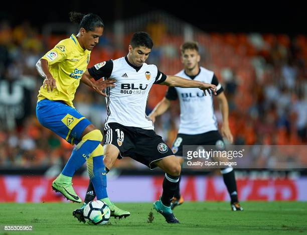 Carlos Soler of Valencia competes for the ball with Mauricio Lemos of Las Palmas during the La Liga match between Valencia and Las Palmas at Estadio...