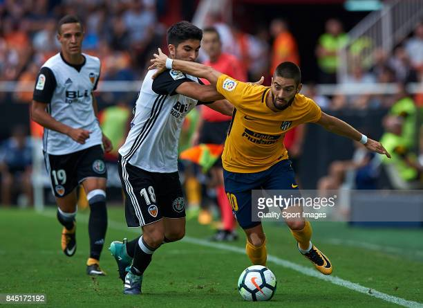 Carlos Soler of Valencia competes for the ball with Yannick Carrasco of Atletico Madrid during the La Liga match between Valencia CF and Atletico...