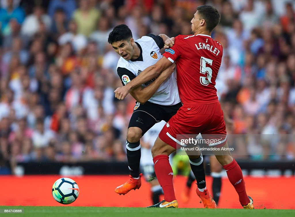Carlos Soler of Valencia is tackled by Clement Lenglet of Sevilla during the La Liga match between Valencia and Sevilla at Estadio Mestalla on October 21, 2017 in Valencia, Spain.