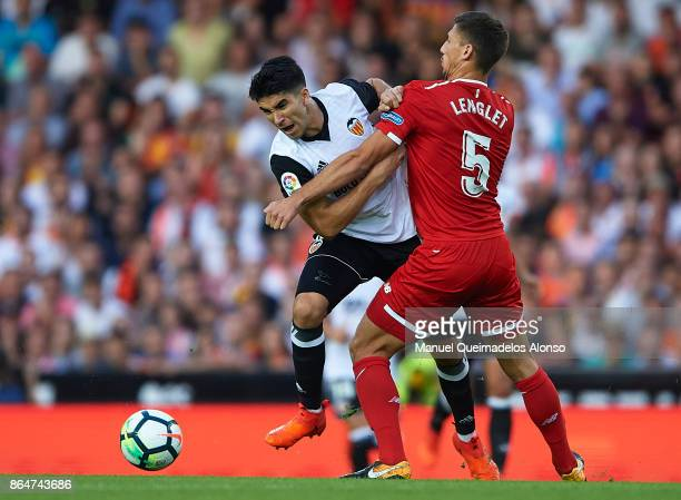 Carlos Soler of Valencia is tackled by Clement Lenglet of Sevilla during the La Liga match between Valencia and Sevilla at Estadio Mestalla on...