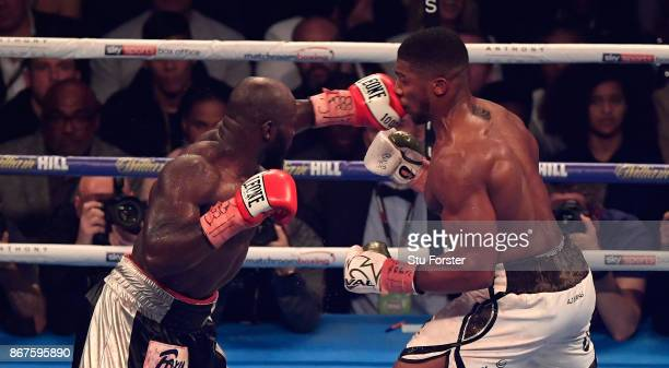 Carlos Takam lands a punch on Anthony Joshua during the fight between Anthony Joshua and Carlos Takam for the World Heavyweight Title at Principality...
