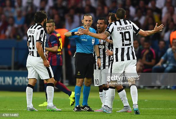 Carlos Tevez and Leonardo Bonucci of Juventus protest with referee Cuneyt Cakir during the UEFA Champions League Final between Juventus and FC...