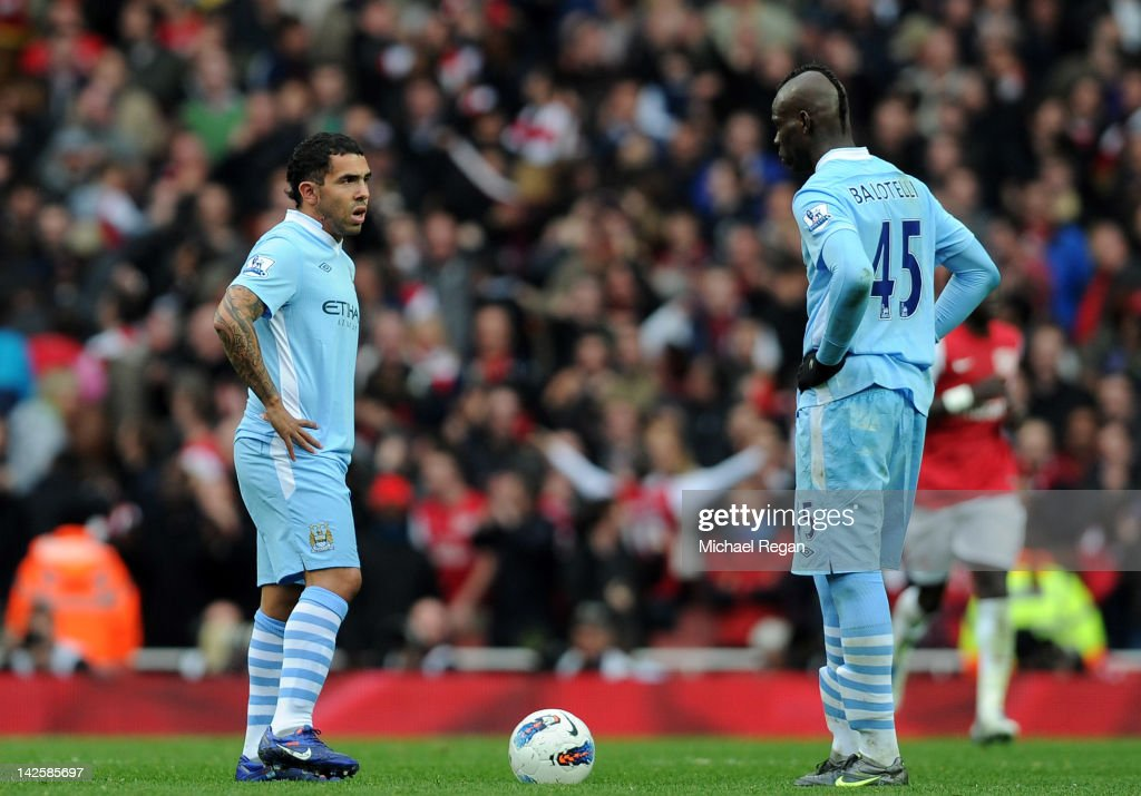 Carlos Tevez and Mario Balotelli of Man City stand dejected after Mikel Arteta of Arsenal scored a goal during the Barclays Premier League match between Arsenal and Manchester City at Emirates Stadium on April 8, 2012 in London, England.
