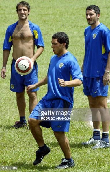 Carlos Tevez del club Boca Junior de Argentina domina el balon observado por sus companeros Raul Cascini y Diego Cana el 30 de junio de 2004 durante...