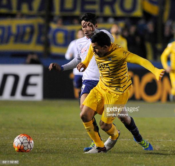 Carlos Tevez of Boca Juniors and Gonzalo Porras of Nacional fight for the ball during a first leg match between Nacional and Boca Juniors as part of...