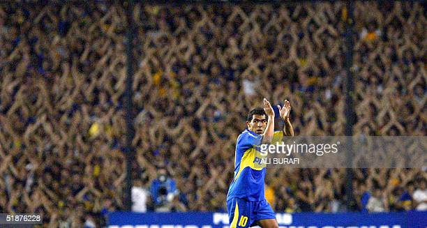 Carlos Tevez of Boca Juniors applauds back at the public as he leaves the field minutes before the end of the Copa Sudamericana final match against...