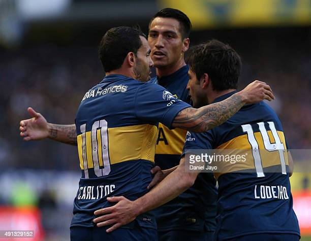 Carlos Tevez of Boca Juniors celebrates with his teammates after forcing an own goal by Gabriel Tomassini of Crucero del Norte during a match between...