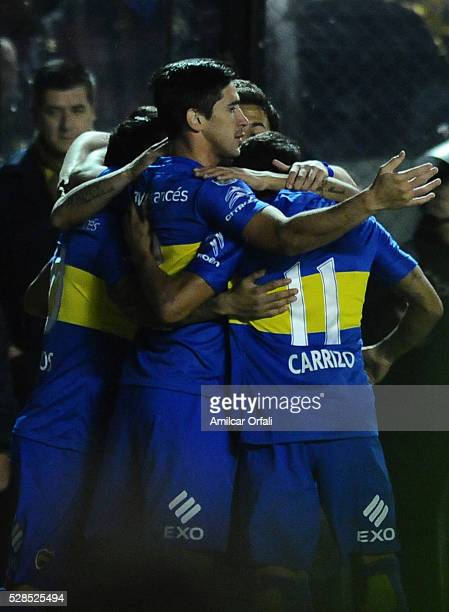 Carlos Tevez of Boca Juniors celebrates with teammates after scoring the first goal of his team by a penalty kick during a second leg match between...