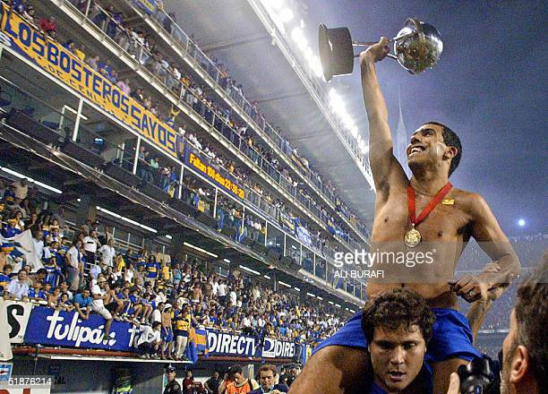 Carlos Tevez of Boca Juniors displays the trophy to the fans after his team defeated Bolivar de La Paz of Bolivia 20 and won the final of Copa...