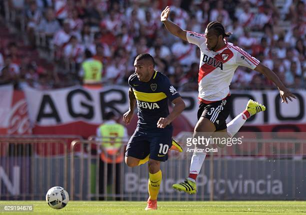 Carlos Tevez of Boca Juniors fights for the ball with Arturo Mina of River Plate during a match between River Plate and Boca Juniors as part of...