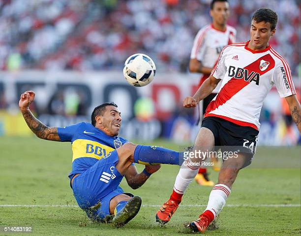 Carlos Tevez of Boca Juniors fights for the ball with Emanuel Mammana of River Plate during a match between River Plate and Boca Juniors as part of...