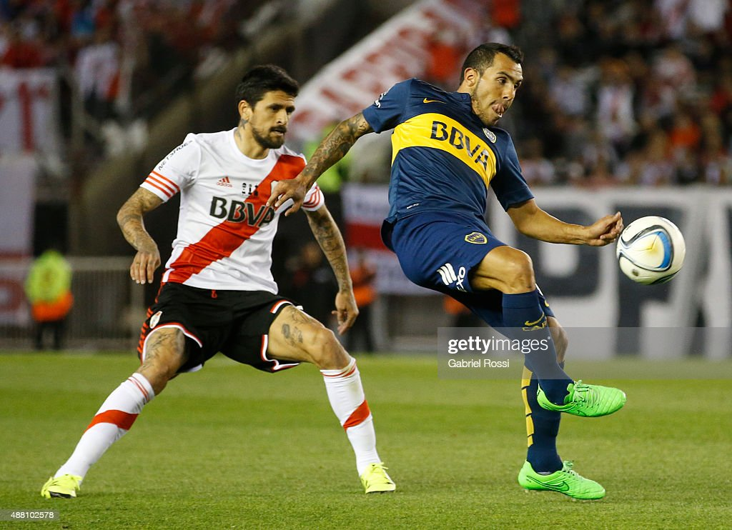 Carlos Tevez of Boca Juniors fights for the ball with Luis Gonzalez of River Plate during a match between River Plate and Boca Juniors as part of 24th round of Torneo Primera Division 2015 at Monumental Antonio Vespucio Liberti Stadium on September 13, 2015 in Buenos Aires, Argentina.