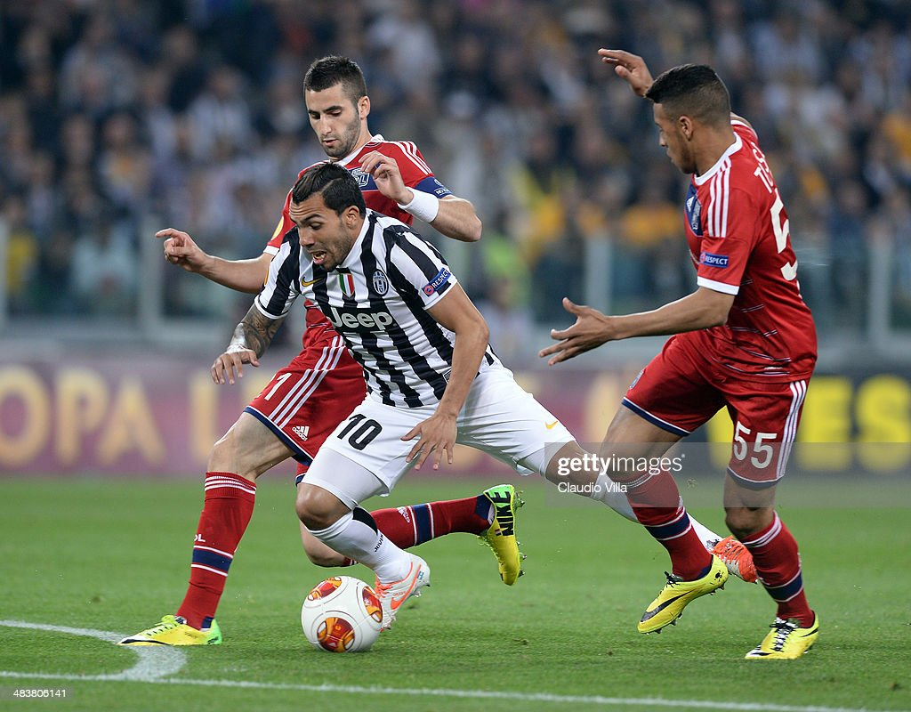 Carlos Tevez of Juventus and Corentin Tolisso of Lyon #55 compete for the ball during the UEFA Europa League quarter final match between Juventus and Olympique Lyonnais at Juventus Arena on April 10, 2014 in Turin, Italy.