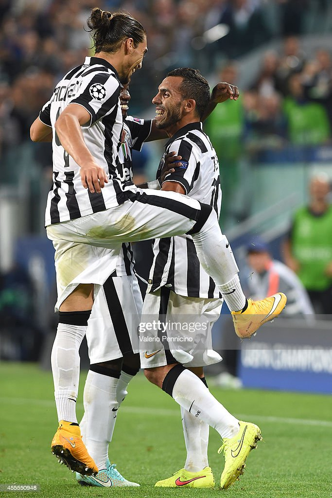 Carlos Tevez (R) of Juventus celebrates his second goal with team-mate during the UEFA Champions League Group A match between Juventus and Malmo FF on September 16, 2014 in Turin, Italy.