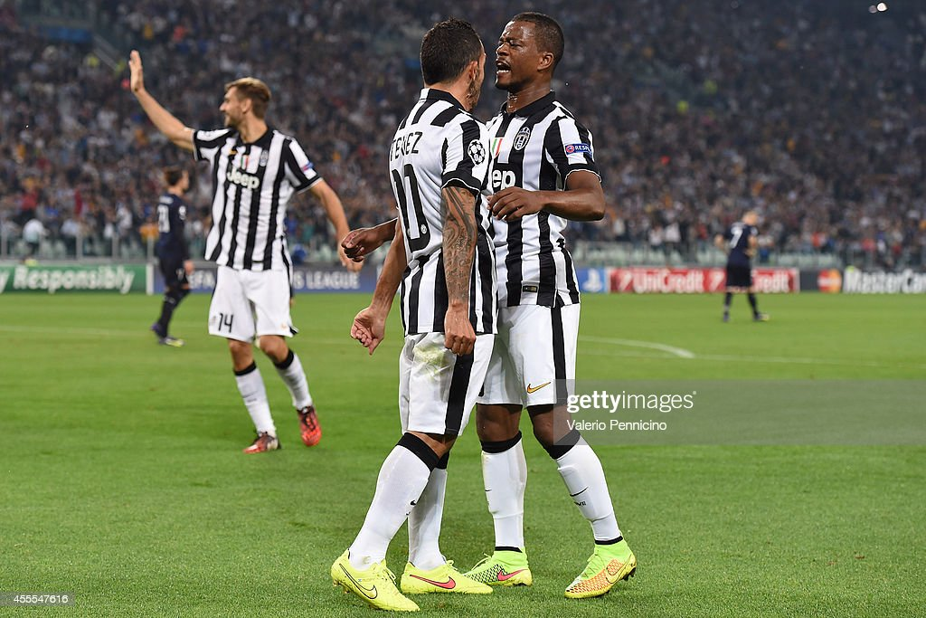 Carlos Tevez (L) of Juventus celebrates the opening goal with team-mates Patrice Evra during the UEFA Champions League Group A match between Juventus and Malmo FF on September 16, 2014 in Turin, Italy.