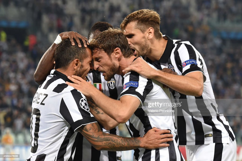 Carlos Tevez of Juventus celebrates the opening goal with teammates Claudio Marchisio during the UEFA Champions League Group A match between Juventus...