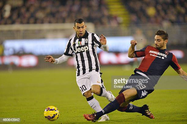 Carlos Tevez of Juventus FC and Marco Capuano of Cagliari in action during the Serie A match at Stadio Sant'Elia on December 18 2014 in Cagliari Italy
