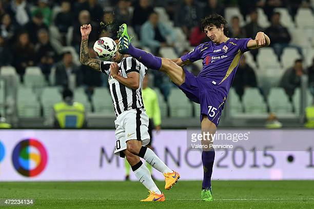 Carlos Tevez of Juventus FC competes with Stefan Savic of ACF Fiorentina during the Serie A match between Juventus FC and ACF Fiorentina at Juventus...