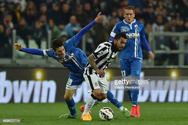 Carlos Tevez of Juventus FC is challenged by Federico Barba of Empoli FC during the Serie A match between Juventus FC and Empoli FC at Juventus Arena...