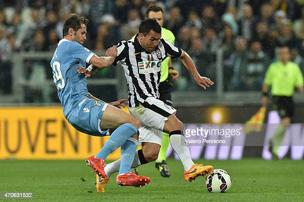 Carlos Tevez of Juventus FC is tackled by Senad Lulic of SS Lazio during the Serie A match between Juventus FC and SS Lazio at Juventus Arena on...