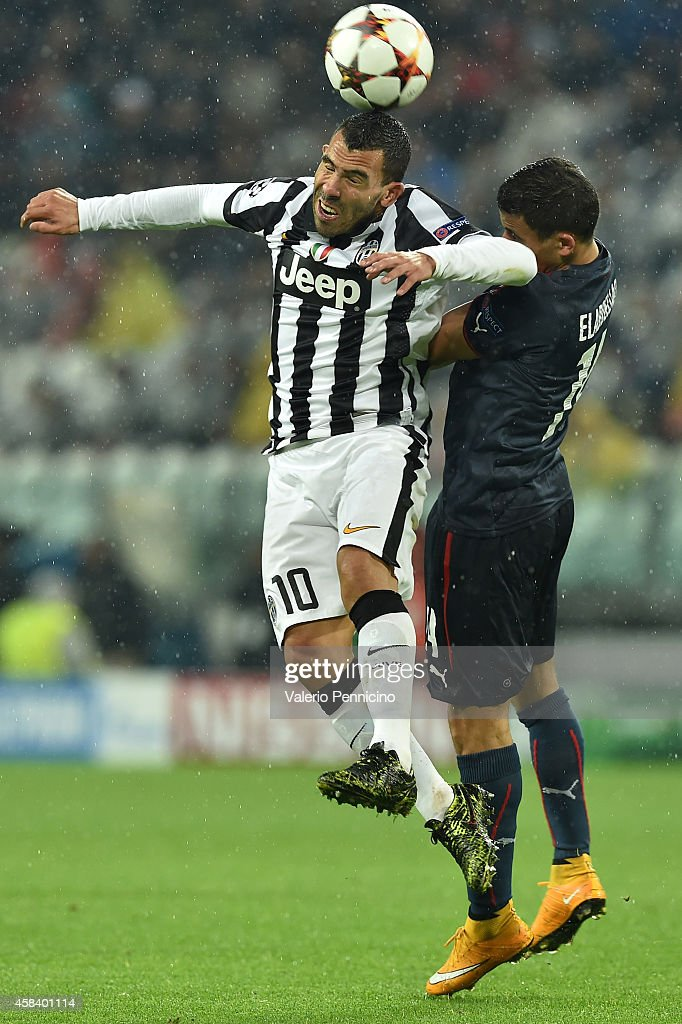 Carlos Tevez (L) of Juventus goes up with Omar Elabdellaoui of Olympiacos FC during the UEFA Champions League group A match between Juventus and Olympiacos FC at Juventus Arena on November 4, 2014 in Turin, Italy.