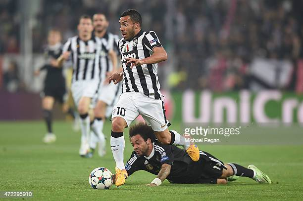 Carlos Tevez of Juventus in action with Marcelo of Real Madrid during the UEFA Champions League semi final match between Juventus and Real Madrid at...