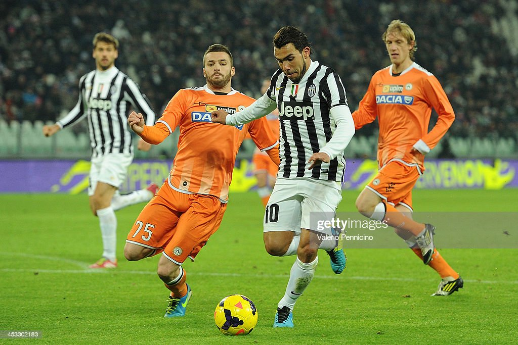 Carlos Tevez (R) of Juventus is challenged by Thomas Heurtaux of Udinese Calcio during the Serie A match between Juventus and Udinese Calcio at Juventus Arena on December 1, 2013 in Turin, Italy.