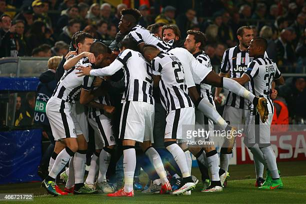 Carlos Tevez of Juventus is mobbed by team mates as he celebrates scoring the opening goal during the UEFA Champions League Round of 16 between...
