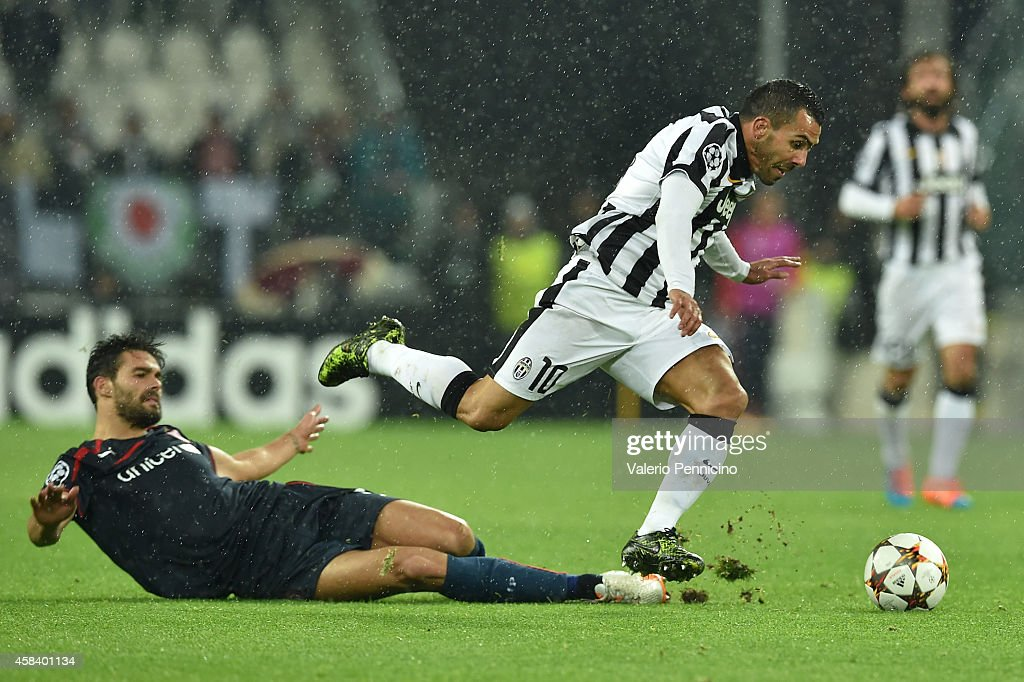 Carlos Tevez (R) of Juventus is tackled by Alberto Botia of Olympiacos FC during the UEFA Champions League group A match between Juventus and Olympiacos FC at Juventus Arena on November 4, 2014 in Turin, Italy.