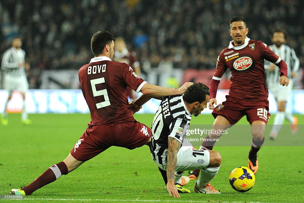 <a gi-track='captionPersonalityLinkClicked' href=/galleries/search?phrase=Carlos+Tevez&family=editorial&specificpeople=220555 ng-click='$event.stopPropagation()'>Carlos Tevez</a> (C) of Juventus is tackled by <a gi-track='captionPersonalityLinkClicked' href=/galleries/search?phrase=Cesare+Bovo&family=editorial&specificpeople=605373 ng-click='$event.stopPropagation()'>Cesare Bovo</a> (L) of Torino FC during the Serie A match between Juventus and Torino FC at Juventus Arena on February 23, 2014 in Turin, Italy.