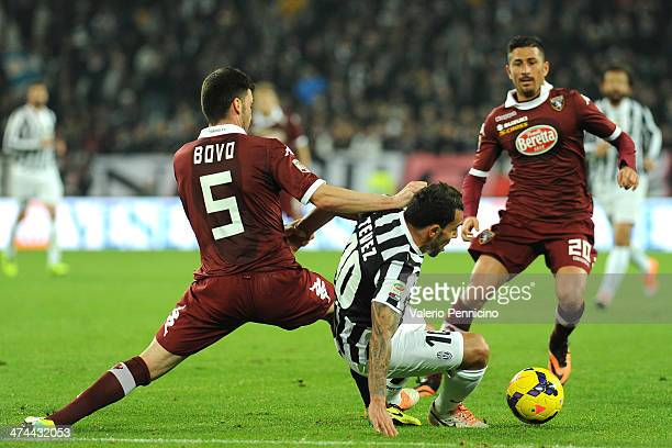 Carlos Tevez of Juventus is tackled by Cesare Bovo of Torino FC during the Serie A match between Juventus and Torino FC at Juventus Arena on February...