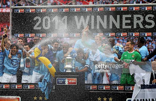 Carlos Tevez of Manchester City and his team mates celebrate with champagne and the trophy after they won the FA Cup sponsored by EON Final match...