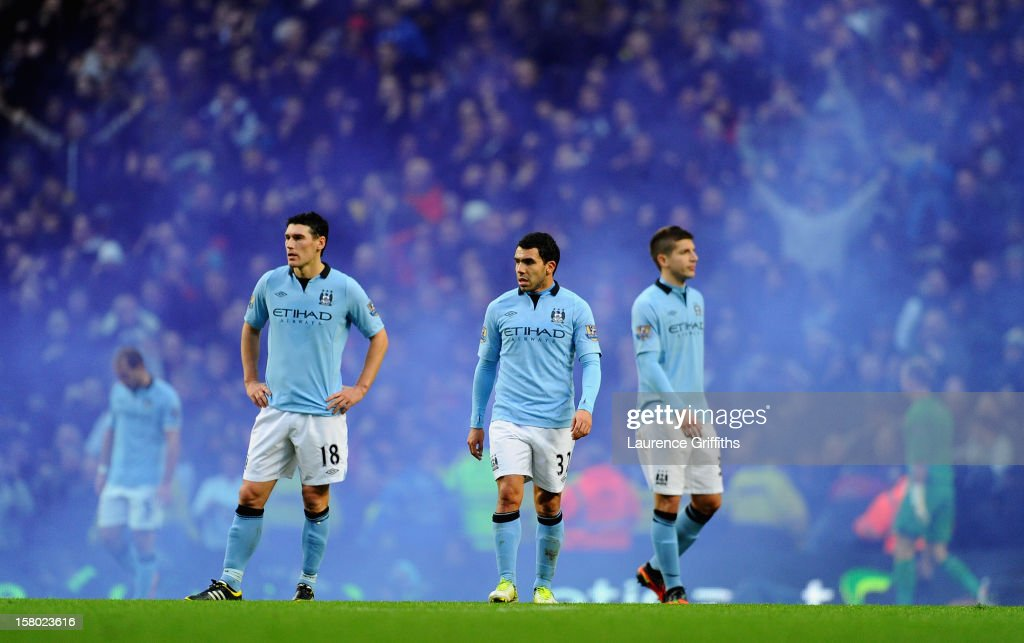 Carlos Tevez of Manchester City and team-mate Gareth Barry look dejected after conceding a third goal during the Barclays Premier League match between Manchester City and Manchester United at the Etihad Stadium on December 9, 2012 in Manchester, England.