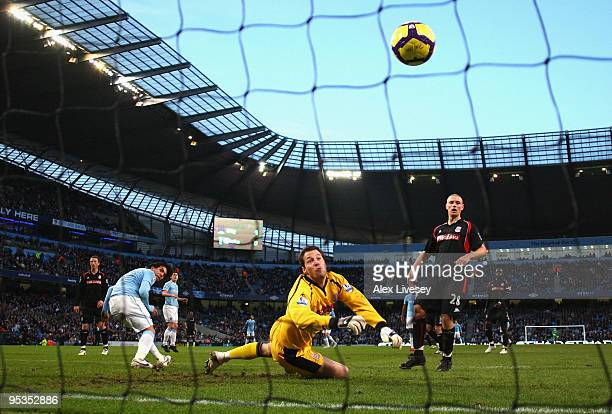 Carlos Tevez of Manchester City beats Thomas Sorensen of Stoke City to score the second goal during the Barclays Premier League match between...