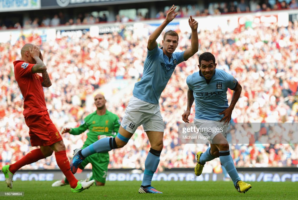 Carlos Tevez of Manchester City celebrates scoring his team's second goal as Martin Skrtel of Liverpool reacts during the Barclays Premier League match between Liverpool and Manchester City at Anfield on August 26, 2012 in Liverpool, England.
