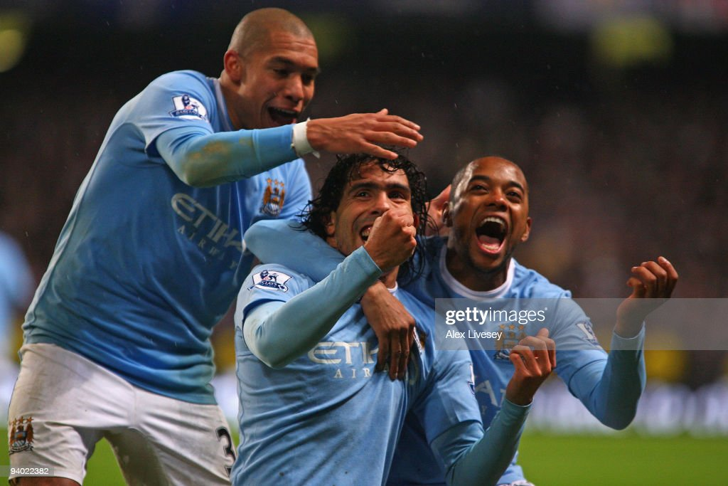 Carlos Tevez of Manchester City celebrates scoring his team's second goal with team mates Robinho and Nigel de Jong during the Barclays Premier...