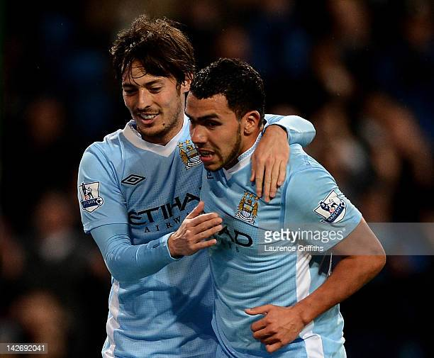 Carlos Tevez of Manchester City celebrates scoring his team's third goal with team mate David Silva during the Barclays Premier League match between...