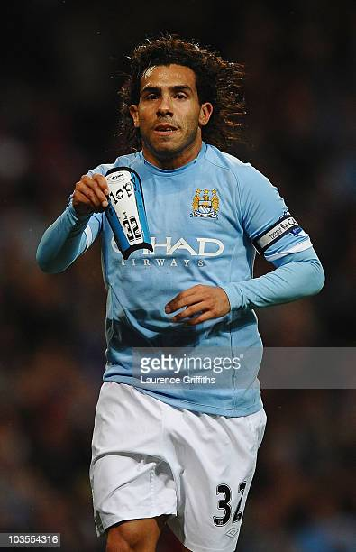 Carlos Tevez of Manchester City celebrates the third goal with James Milner goal during the Barclays Premier League match between Manchester City and...